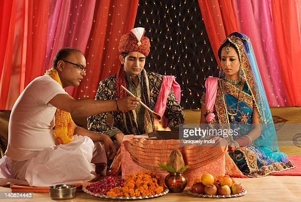 Priest performing religious ceremony in wedding mandap