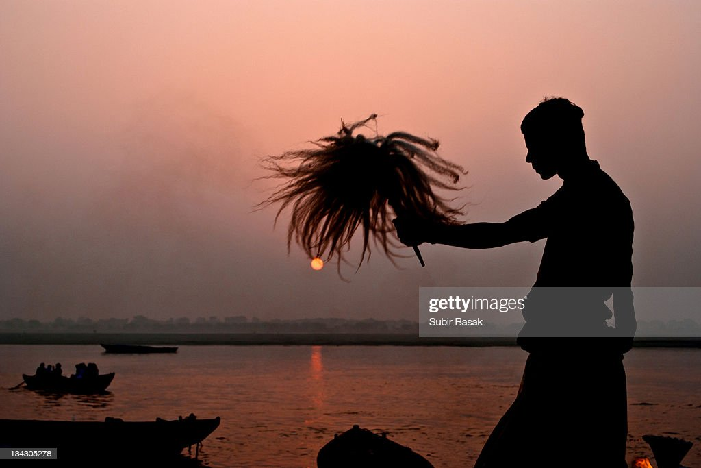 Priest praying during sunrise at Varanasi : Stock Photo