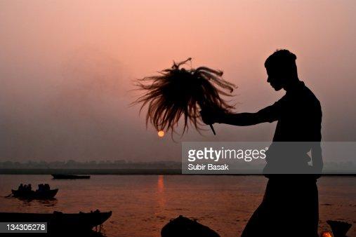 Priest praying during sunrise at Varanasi : Stock Photo