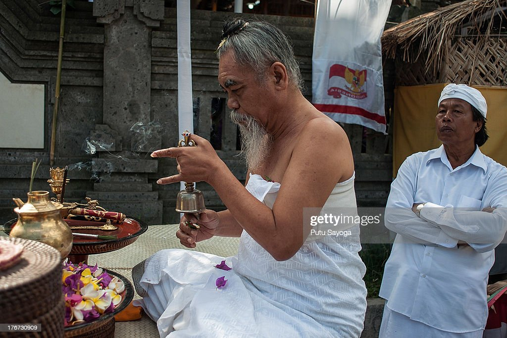 A priest prays during a Balinese Hindu mass cremation on August 18, 2013 in Ubud, Bali, Indonesia. More than 60 corpses were collectively cremated to share the expense of the ceremony. Well known as Ngaben, it is one of the most important ceremonies for Balinese Hindu people, as they believe it will free the spirit from the deceased body so it can reincarnate.