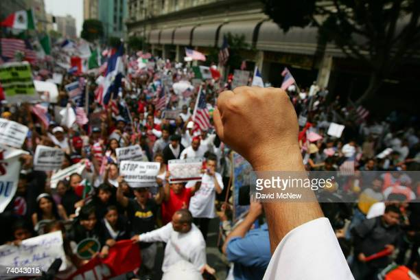 A priest raises his fist while leading a chant for demonstrators marching to City Hall in one of several May Day marches and rallies in southern...