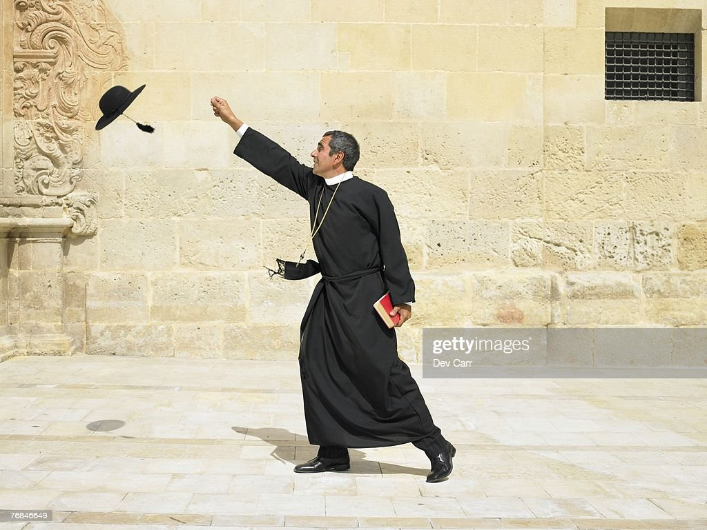 Priest reaching for his hat blowing in the wind, Alicante, Spain,