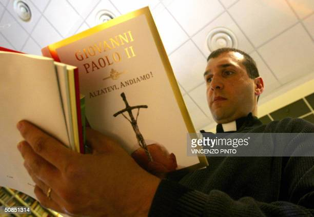 A priest reads Pope John Paul II's new book 'Alzatevi andiamo' in a bookshop at the Vatican 18 May 2004 The pontiff who celebrates 18 May 2004 his...
