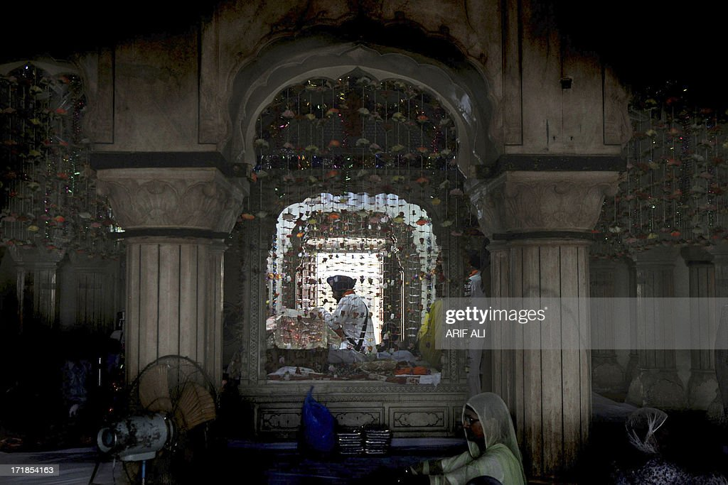 A priest reads the Sikh holy book, the Guru Granth Sahib, while pilgrims gather at a shrine in Lahore on June 29, 2013, on the 174th death anniversary of Maharaja Ranjit Singh. Singh was also known as 'Sher-e-Punjab' or 'Lion of Punjab' and is remembered for uniting the Punjab as a strong nation and his possession of the Koh-i-noor diamond. Singh, who was born in Gujranwala in 1780, was the ruler of the Pakistani Punjab province and died on June 27, 1839. AFP PHOTO/Arif ALI