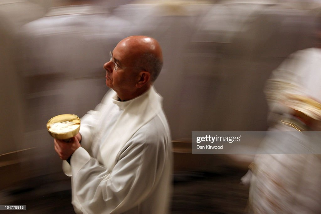 A priest serves holy communion after Pope Francis conducted his first Chrism Mass inside St Peter's Basilica on the morning of Holy Thursday on March 28, 2013 in Vatican City, Vatican. Pope Francis is currently taking part in his first holy week as pontiff. The pope's first holy week will also incorporate him washing the feet of prisoners in a youth detention centre later today.