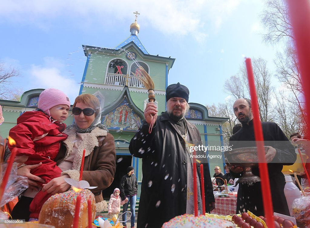 A priest sprinkles Holy water as he blesses Easter cakes (kulichs) and eggs on Orthodox Holy Saturday at a church in Saint-Petersburg , Russia on April 29, 2016.