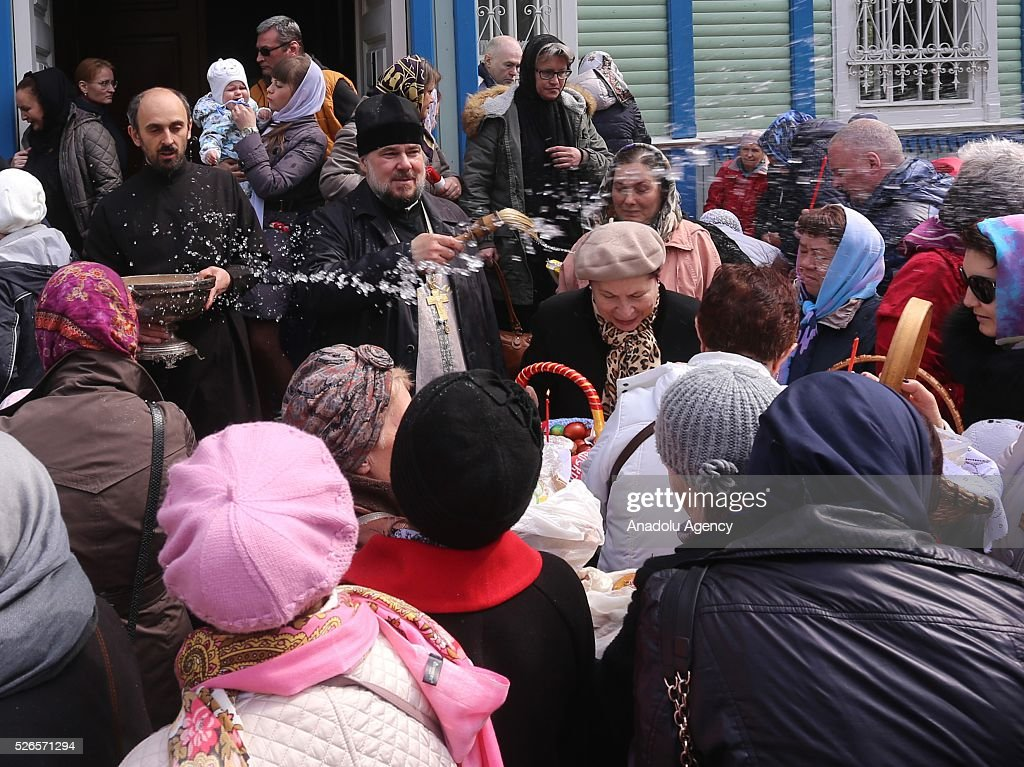 A priest sprinkles Holy water as he blesses Orthodox Christian believers on Orthodox Holy Saturday at a church in Saint-Petersburg , Russia on April 29, 2016.