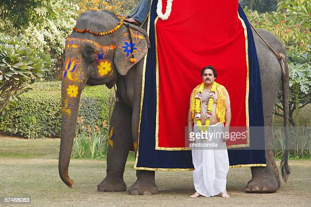 Priest standing beside an elephant