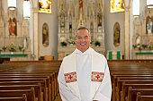 Priest standing in ornate church