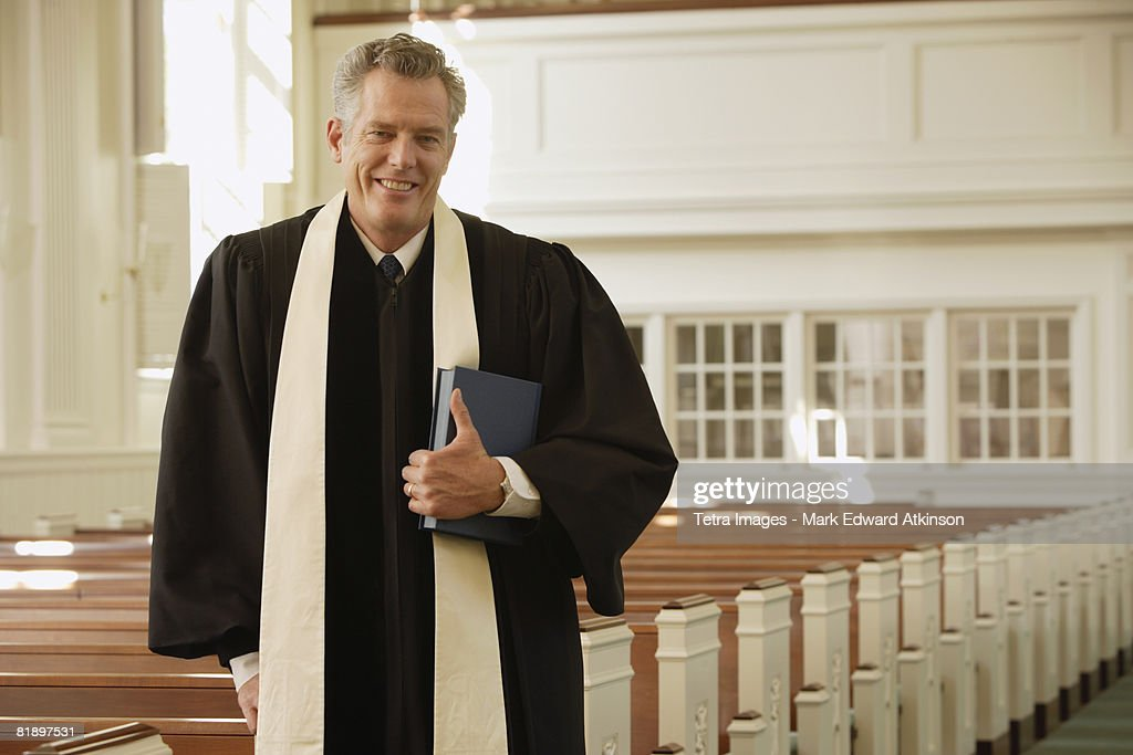 Priest standing next to pews : Stock Photo