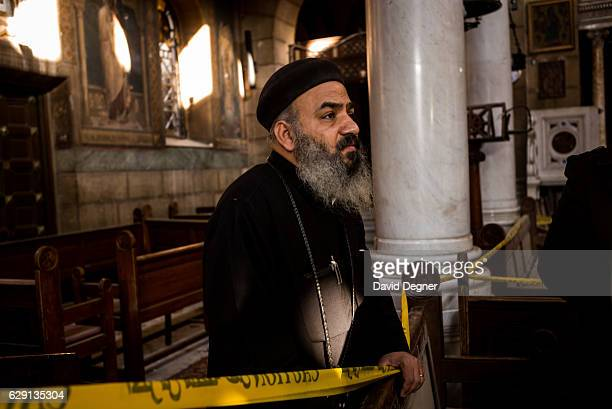 A priest stands in the church at the site of the bombing on December 11 2016 in Cairo Egypt A bomb exploded inside the Saint Mark's Coptic Orthodox...