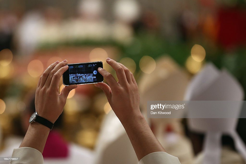 A priest takes a photograph as Pope Francis conducts his first Chrism Mass inside St Peter's Basilica on the morning of Holy Thursday on March 28, 2013 in Vatican City, Vatican. Newly-appointed Pope Francis has begun the Christian traditions leading up to Easter during his first holy week as pontiff. Pope Francis will today hold a feet-washing mass, which commemorates the last supper, at a youth detention centre where he will wash the feet of prisoners.