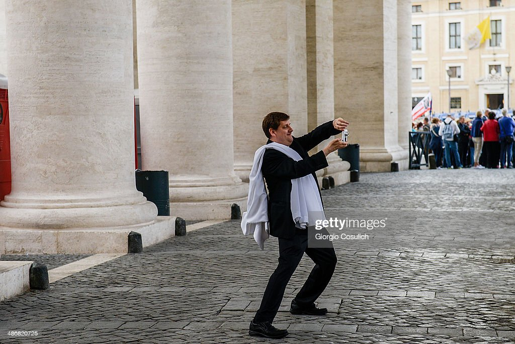 A priest takes a picture under the colonnade of Saint Peter's Square on April 26, 2014 in Vatican City, Vatican. The late Popes John Paul II and John XXIII will be canonised on April 27 inside the Vatican with 800,000 pilgrims from around the world expected to attend.