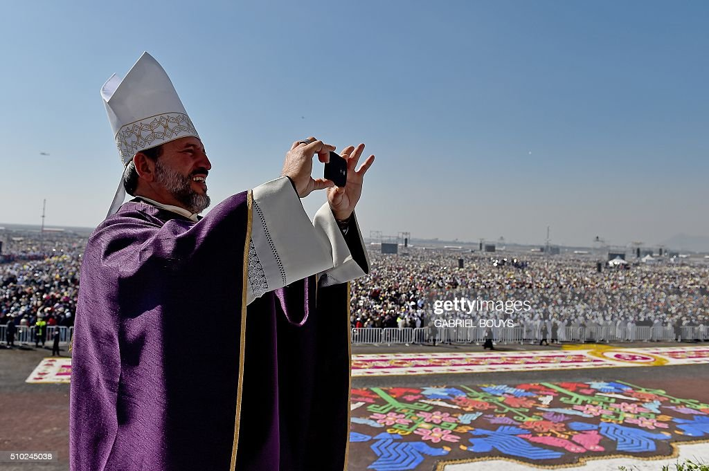 A priest takes a snapshot as he waits for Pope Francis to celebrate an open-air mass at the Study Center in Ecatepec, near Mexico City on February 14, 2016. Pope Francis waded into one of Mexico's most dangerous cities on Sunday to celebrate an open-air mass with more than 300,000 Catholic faithful longing for a message of peace. AFP PHOTO / GABRIEL BOUYS / AFP / GABRIEL BOUYS