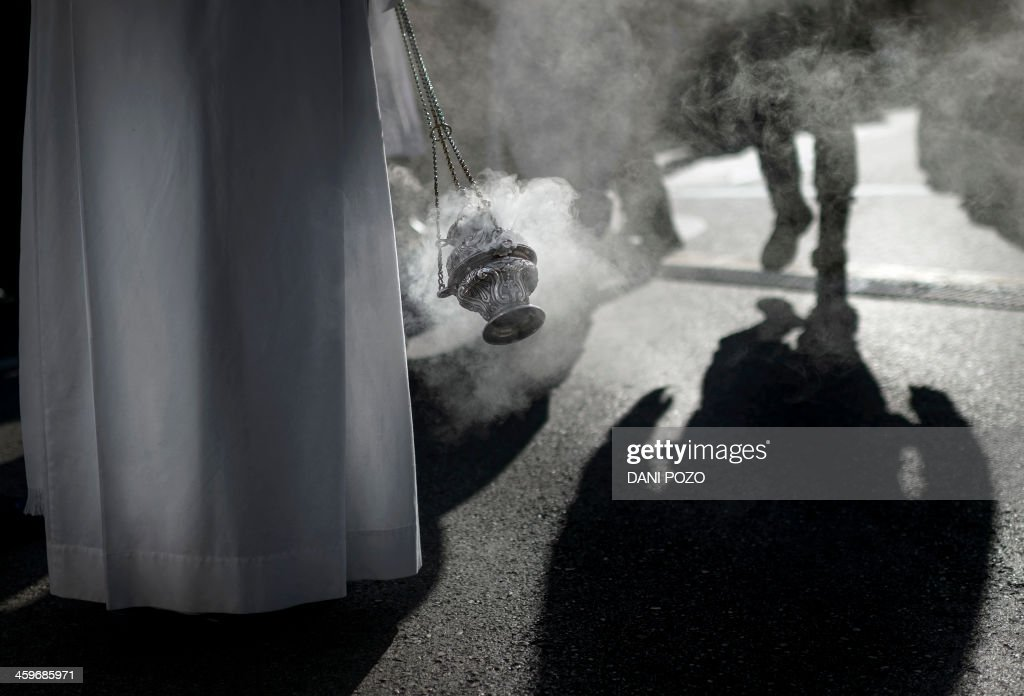 A priest takes part in the mass for the Holy Family in Madrid on December 29 2013 Tens of thousands of believers poured into central Madrid to...