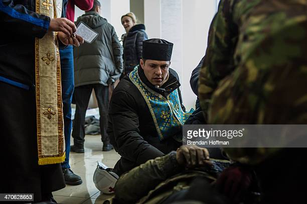 A priest tends to a wounded antigovernment protester in the lobby of the Hotel Ukraine which has been converted to a medical clinic and makeshift...