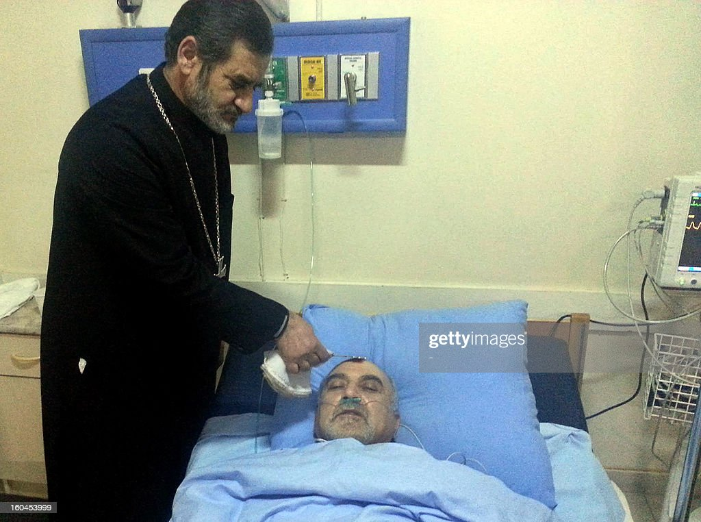 A priest visits Armenian presidential candidate, head of the Union for National Self-Determination, Paruyr Hayrikyan in a hospital room in Yerevan, early on February 1, 2013. Paruyr Hayrikyan was shot and wounded late yesterday by an unknown assailant in the capital Yerevan less than a month before election day, police said.