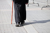 Legs of monk in a black robe on sidewalk, cleric outdoors