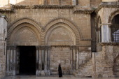 A priest walks past the entry of The Church of the Holy Sepulchre also known as the Basilica of the Resurrection Christianity's holiest site in...