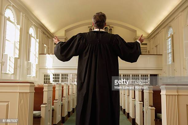 Priest with arms raised in church