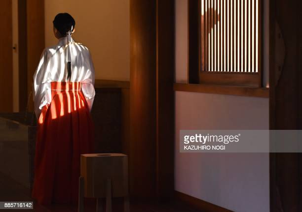 A priestess waits for lawmakers visiting the controversial Yasukuni shrine in Tokyo on December 5 2017 Dozens of Japanese parliament members on...