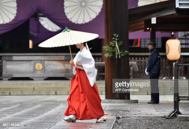 TOPSHOT A priestess walks at the controversial Yasukuni Shrine in Tokyo on October 17 2017 Abe sent a ritual offering to a controversial war shrine...