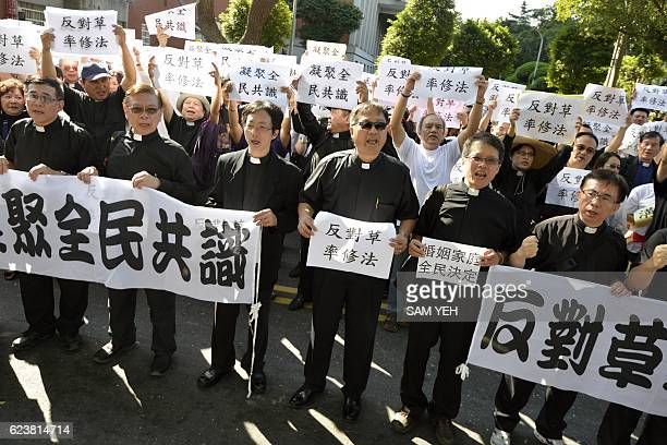 Priests from various religious groups display banners and placards that read 'stand forward for the next generation's happiness' during a...