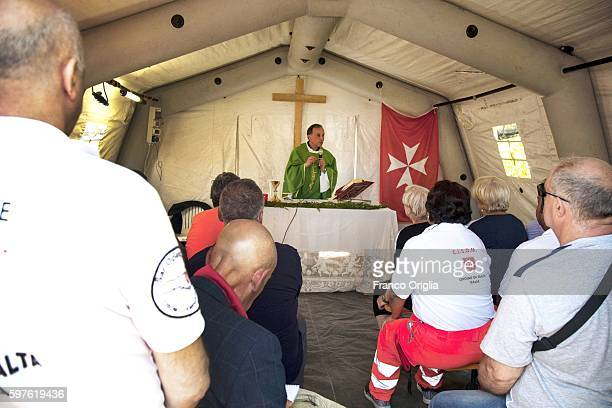 A priests hold a mass in the first aid camp of the Sovereign Military Order of Malta after the earthquake hit the town on August 28 2016 in Rieti...