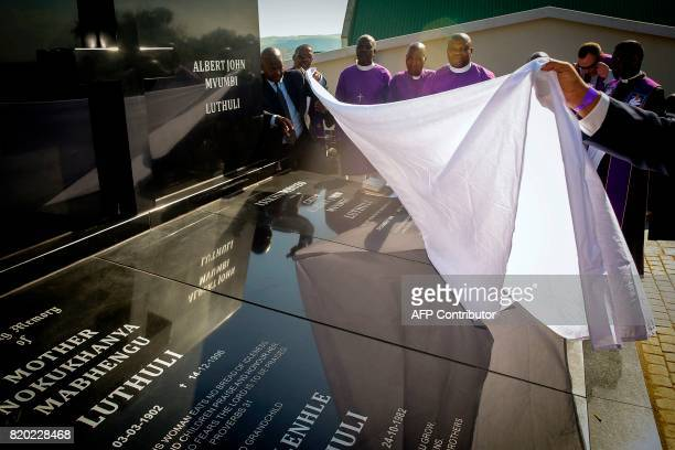 Priests lay a white sheet over the grave of late Chief Albert Luthuli during a commemoration under theme of unity in action marking the 50th...