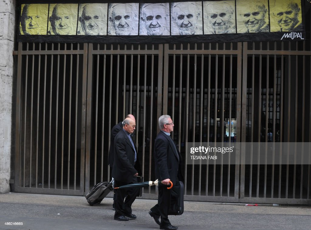 Priests pass near a new work of an Italian street artist Maupal, a portrait of the three popes, Pope Francis (C) Pope John Paul II (R) and Pope John XXIII (L) on April 23, 2014 in Rome near the Vatican. AFP PHOTO / TIZIANA FABI CAPTION =