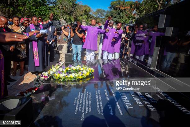 Priests raising hands pray over the grave of late Chief Albert Luthuli during a commemoration under theme of unity in action marking the 50th...