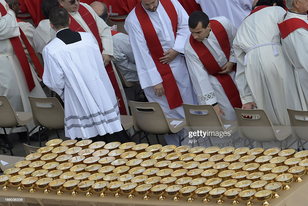 Priests take place past communion chalices as they arrive for the Holy mass with the ecclesial movements for Pentecost Sunday on May 19, 2013, at St peter's square at the Vatican. AFP PHOTO / ANDREAS SOLARO
