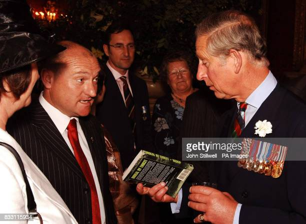 Priince Charles the Prince of Wales is given a book by former Royal Navy Seaman Andrew Gatherer about the sinking of his ship HMS Glamorgan during a...