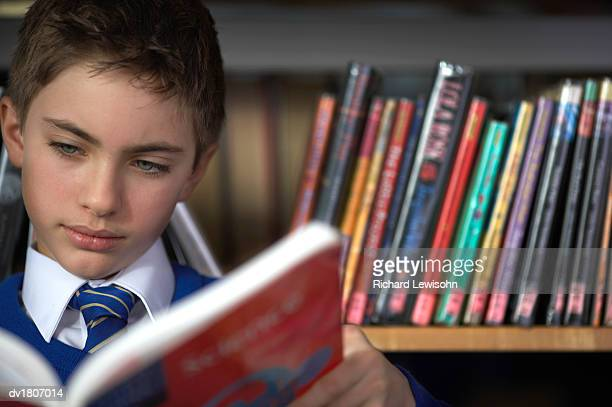 Primary School Boy Reads a Book With Concentration in Front of a Book Shelf