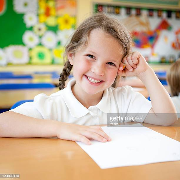 primary school: bright smile from happy young schoolgirl in class