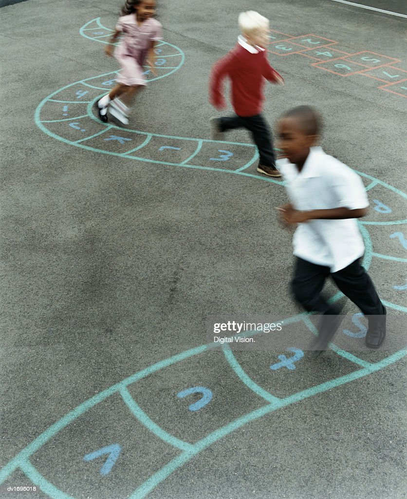 Primary School Children Chasing Each Other in a School Playground : Stock Photo