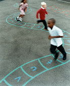 Primary School Children Chasing Each Other in a School Playground