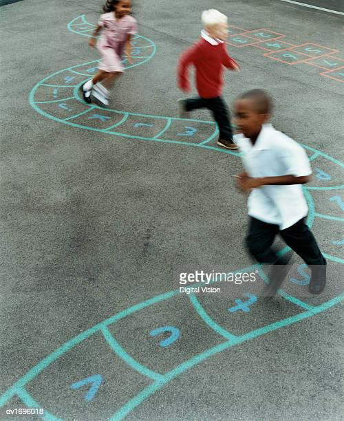Primary School Children Chasing Each Other in a School Playground