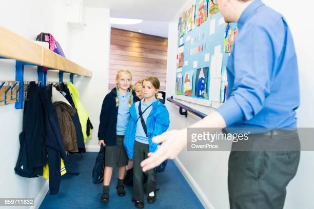 UK primary School children hanging coats.