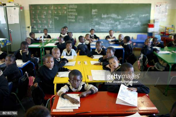Primary school children listens to their teacher during an English class on May 10 2007 in Orlando West district of Soweto South Africa Many of the...