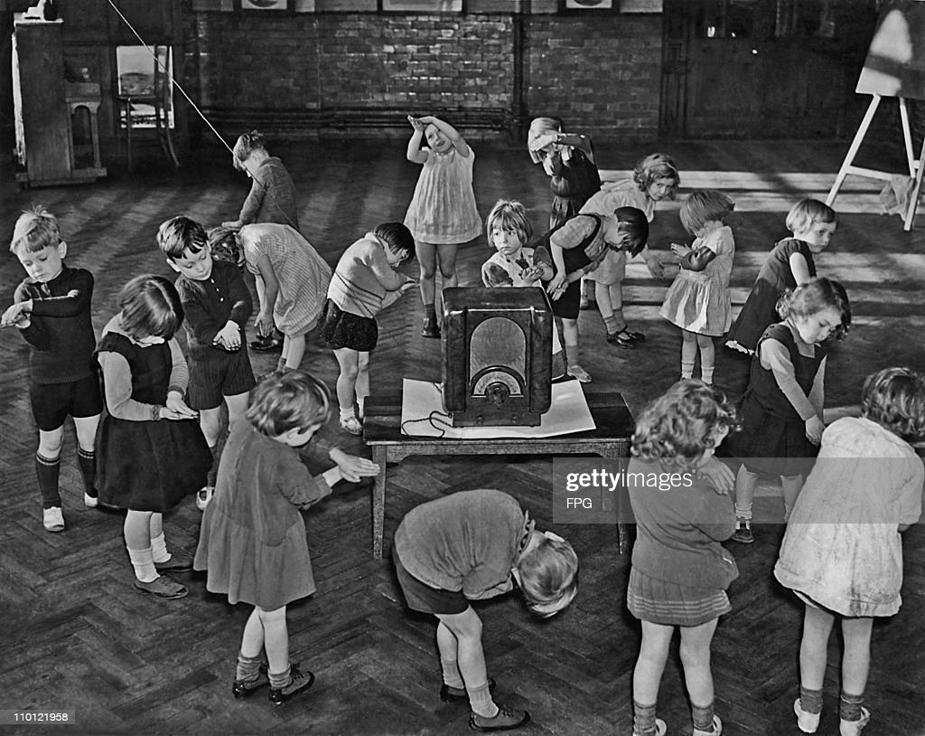 Primary school children performing their own actions to go with a BBC 'Music And Movement' programme on the radio, London, circa 1935.