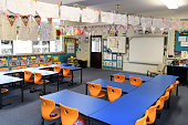 Empty tables and chairs in class with whiteboard and educational equipment. Artwork hanging up on clothes line inside