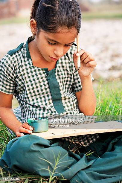 Primary school girl writing & studying outdoor