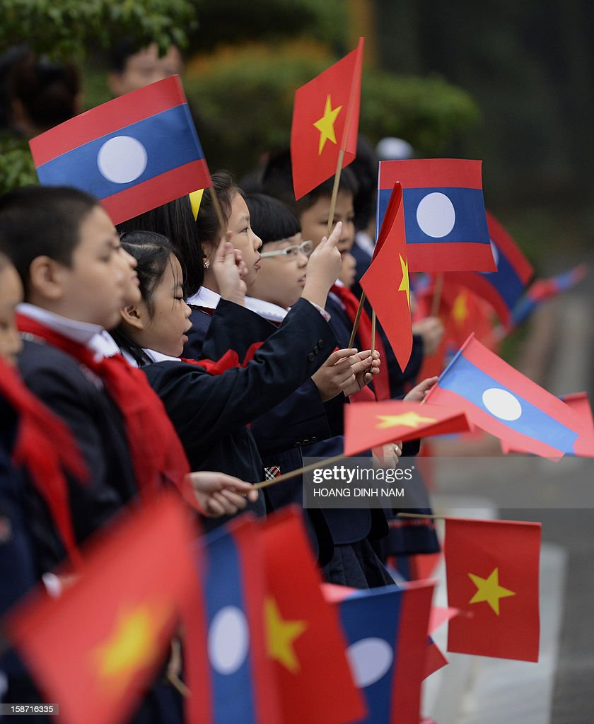 Primary school pupils hold Vietnamese and Lao flags prior to the arrival of the visiting Lao President Choummaly Sayasone (not pictured) for a welcoming ceremony at the presidential palace in Hanoi on December 26, 2012. The three-day visit by the Lao leader is part of celebrations marking the 50th anniversary of the diplomatic relations between the two Southeast Asian communist nations. AFP PHOTO/HOANG DINH Nam