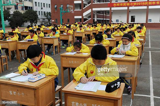 Primary school students compete calligraphy on the playground on January 13 2015 in Dongyang of Jinhua City Zhejiang Province of China Pupils of...