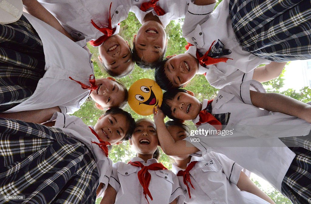 Primary school students in Yongchuan District hold a board of smiling face to welcome the upcoming World Smile Day on May 5, 2016 in Chongqing, China.