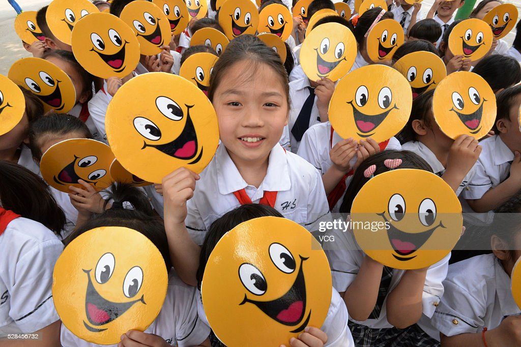 Primary school students in Yongchuan District hold boards of smiling faces to welcome the upcoming World Smile Day on May 5, 2016 in Chongqing, China.