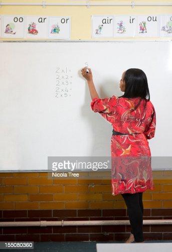 A primary school teacher in the classroom. : Stock Photo