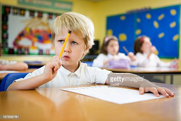 primary school: young boy concentrating over a challenging maths problem