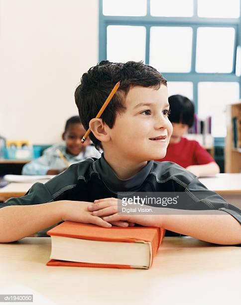 Primary Schoolboy Sitting at His Desk and Looking Sideways